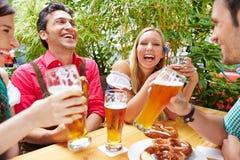 Friends having fun in beer garden. Friends drinking beer and having fun in beer garden in Bavaria royalty free stock images