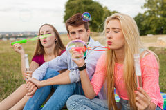 Friends having fun and blowing soap bubbles in park. Stock Images
