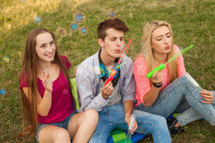 Friends having fun and blowing soap bubbles in park. Stock Image