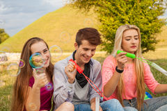 Friends having fun and blowing soap bubbles in park. Royalty Free Stock Images