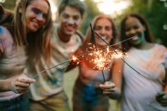 Friends having fun burning fire sparkle sticks after playing hol stock image