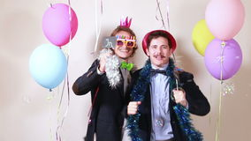 Friends having fun dancing with boards in love in photo booth. Two male friends having fun dancing with boards in love in party photo booth stock footage
