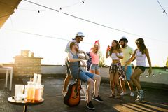 Friends having fun and drinking cocktails outdoor on a rooftop get together royalty free stock image