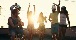 Friends having fun and drinking outdoor on a rooftop get together royalty free stock image