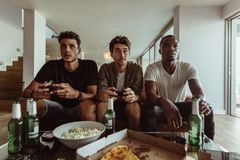 Friends playing video game sitting at home Stock Photo