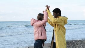 Friends having fun and enjoy together on the beach. Two multicultural free person of black male and attractive european female. Lovers clap hands slow motion stock video footage
