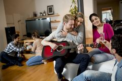 Friends having fun with guitar stock image