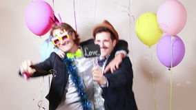 Friends having fun holding boards in love in photo booth stock video footage