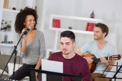 Friends having fun at home singing song together Royalty Free Stock Photos