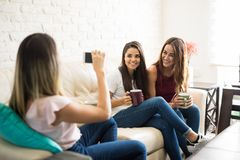 Friends having fun at home. Three cute female friends having some fun together at home and taking photos to each other Royalty Free Stock Photos