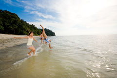Friends having fun jumping into the sea Stock Images