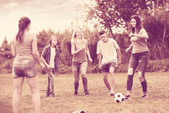 Friends having fun and kicking football Stock Photography
