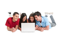 Friends having fun at laptop. Happy smiling young group of friends watching and working together at laptop isolated on white background Royalty Free Stock Photos