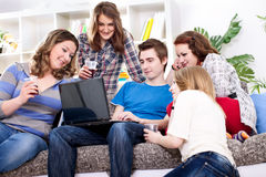 Friends having fun with laptop. Group of friends playing on internet in living room Stock Image