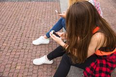 Friends having fun, listening to music and relax in park. Happy teenage girls spend time in the city. royalty free stock image