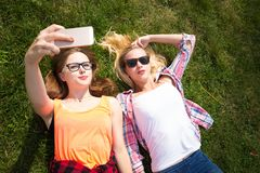 Friends having fun, listening to music and relax in park. Happy teenage girls spend time in the city. stock images