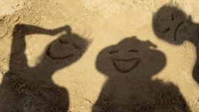 Friends having fun making faces on a sandy beach royalty free stock image