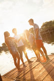 Friends Having Fun Near Lake. Group Of Cheerful Friends Having Fun Near Lake royalty free stock photography