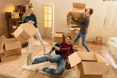 Friends having fun in new house while unpacking things Royalty Free Stock Photo