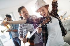 Friends having fun and partying in house and playing music. Group of Friends having fun and partying in house and playing music Royalty Free Stock Photography