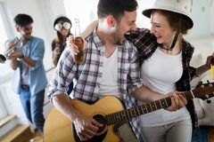 Friends having fun and partying in house and playing music stock photo