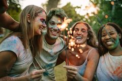 Group of friends burning fire sparkles while playing holi royalty free stock photography