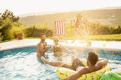 Friends having fun at a poolside party. Group of friends at a poolside summer party, having fun in the swimming pool, drinking beer and splashing water stock photo