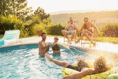 Friends having fun at a poolside party. Group of friends at a poolside summer party, having fun in the swimming pool, drinking beer and splashing water royalty free stock images