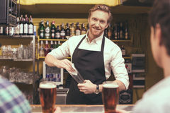 Friends having fun in pub. Football time. Friends spending time together in pub. Guys having fun while drinking beer. Barman looking at camera and wiping glass Royalty Free Stock Image