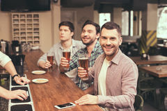 Friends having fun in pub. Football time. Friends spending time together in pub. Guys having fun while watching football. Men drinking beer Stock Photography