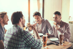 Friends having fun in pub. Pizza time. Friends spending time together in restaurant. Guys drinking beer and eating pizza Royalty Free Stock Photos