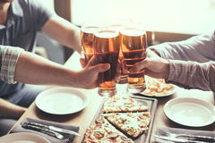 Friends having fun in pub. Pizza time. Friends spending time together in restaurant. Guys drinking beer and eating pizza Royalty Free Stock Photography