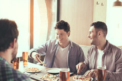 Friends having fun in pub. Pizza time. Friends spending time together in restaurant. Guys drinking beer and eating pizza Stock Image
