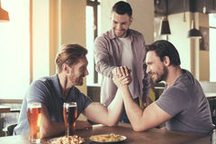 Friends having fun in pub. Pizza time. Friends spending time together in restaurant. Guys drinking beer and eating pizza. Men wrestling Royalty Free Stock Photos