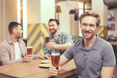 Friends having fun in pub. Pizza time. Friends spending time together in restaurant. Guys drinking beer and eating pizza. One men smiling and looking at camera Stock Image