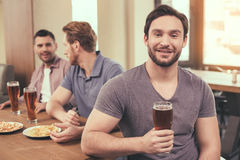 Friends having fun in pub. Pizza time. Friends spending time together in restaurant. Guys drinking beer and eating pizza. One men smiling and looking at camera Stock Photo