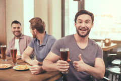 Friends having fun in pub. Pizza time. Friends spending time together in restaurant. Guys drinking beer and eating pizza. One men smiling, showing thumb up and Stock Photo