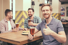 Friends having fun in pub. Pizza time. Friends spending time together in restaurant. Guys drinking beer and eating pizza. One men smiling, showing thumb up and Stock Photography