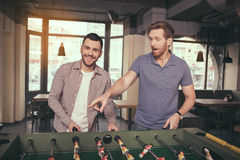 Friends having fun in pub. Table football. Friends spending time together in pub. Guys having fun while playing table football Royalty Free Stock Image