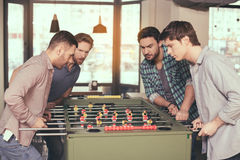 Friends having fun in pub. Table football. Friends spending time together in pub. Guys having fun while playing table football Stock Photography