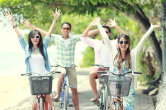 Friends having fun riding bicycle together. Carefree group friends having fun and smiling riding bicycle during the summer day stock photography