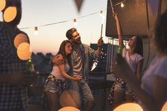 Friends having fun at a rooftop party royalty free stock image