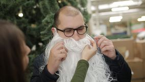 Friends try on the beard of Santa. Friends having fun on sale Christmas decorations. stock footage