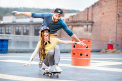 Friends having fun with skateboard outdoors Stock Photography