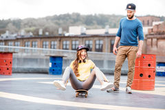 Friends having fun with skateboard outdoors Stock Photo