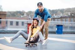 Friends having fun with skateboard outdoors Stock Photos