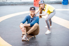 Friends having fun with skateboard outdoors Stock Images