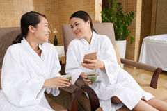 Friends Having Fun in Spa Center. Pretty Asian women spending weekend in spa center: they sitting on comfortable armchairs, drinking herbal tea and looking stock image