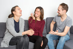 Friends having fun. Three adult persons sitting laughing in living room stock photo