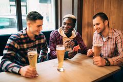 Friends having fun. Three happy young men in casual wear drinking beer in pub while one of looking phone and smiling stock image
